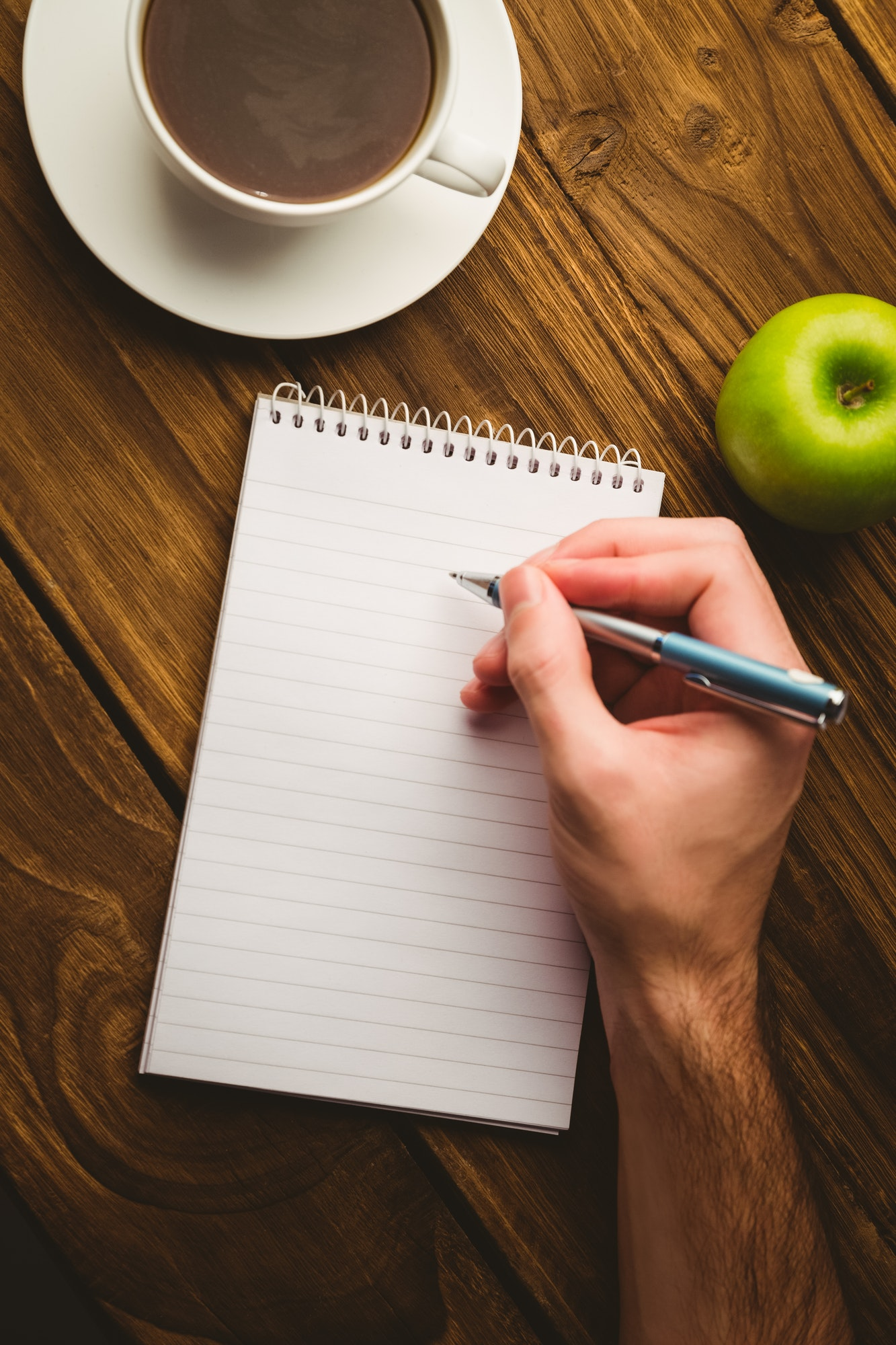 Hand writing on the notepad on a desk